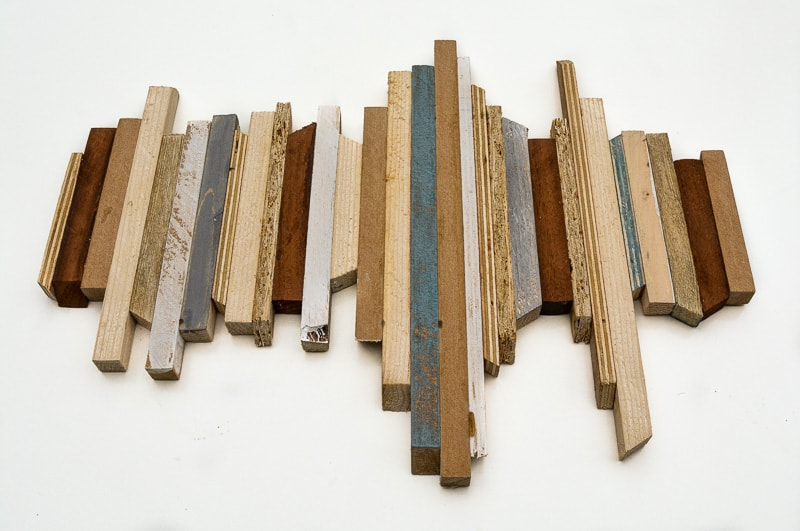 You can make DIY Wooden Wall Art for your home, with this super easy step by step tutorial. Using a variety of scrap wood you can build this DIY wood wall art.