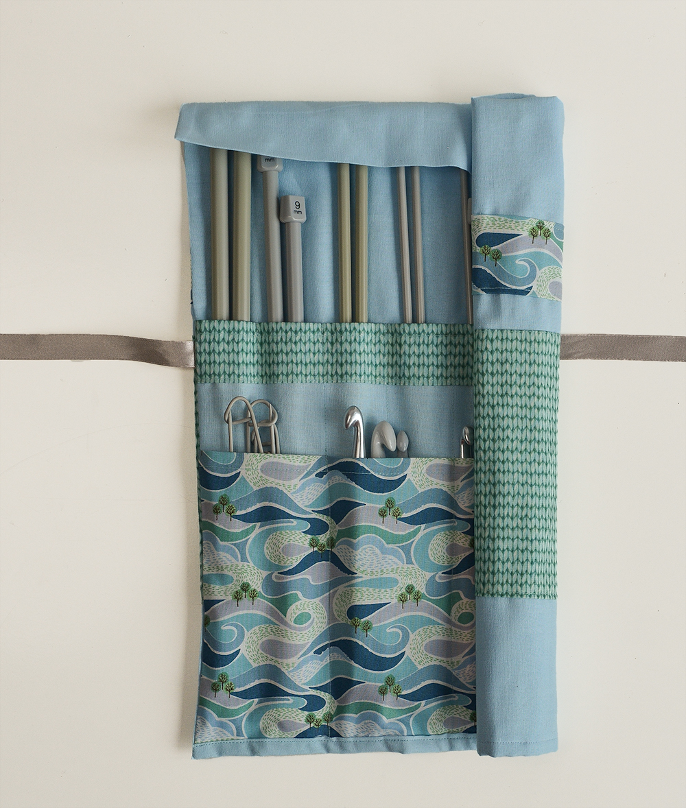 This knitting needle case tutorial uses one long piece of fabric, which is folded to create roll with a pocket for the knitting needles and a smaller pocket for round knitting needles, cable needles and crochet hooks.